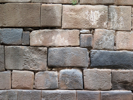 Inca wall made of natural volcanic stones, perfectly shaped, heritage of Inca history and architecture in Cusco, Peru. Stock Photo