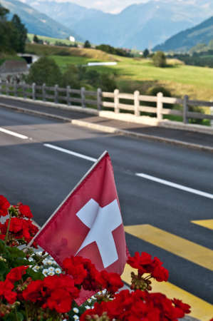 switzerland flag in a typcal mountain landscape