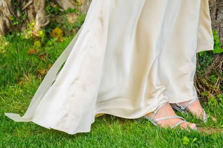 wedding shoes and dress in the grass