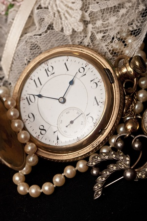 A gold Vintage Pocket Watch adorned with pearls and diamonds, sits atop some lace.
