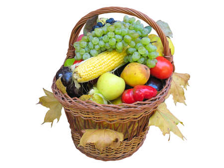 Wicker basket with autumn fruit and vegetables isolated over white background photo