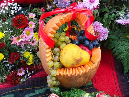 pumpkin basket with autumn harvest fruit and vegetables photo