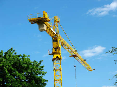 erect: yellow building crane over blue sky background