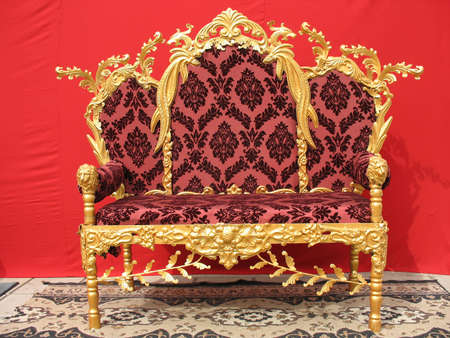 Ornated golden sofa furniture over red background photo