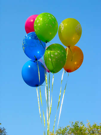 Bunch of colored party balloons against blue sky background photo