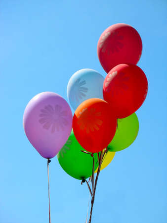 Group of colorful celebration or birthday barty balloons over blue sky background photo