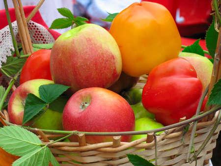 Harvesting apples, leaves and sweet peppers in a wooden basket Standard-Bild
