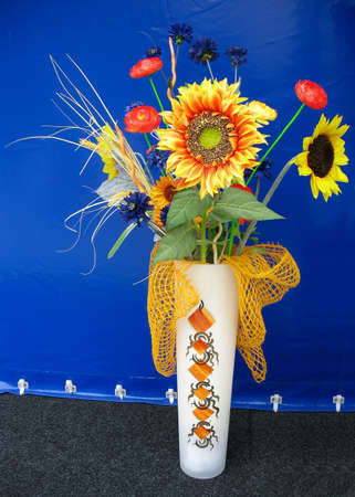 Yellow and red sunflower decor composition in a vase over blue backgruond photo
