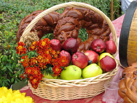 Harvesting apples, bread and flowers in a wooden basket photo