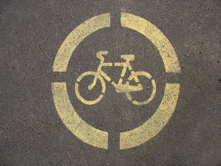 Yellow sign of a bicycle on the asphalt pavement background Stock Photo - 6929213