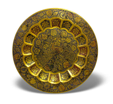 Old golden plate with oriental ornament over white background photo