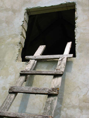 Old wooden ladder to window over the wall background photo