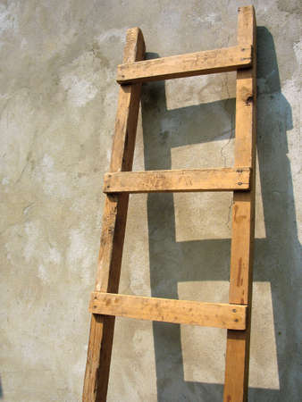 Old wooden ladder over the wall background