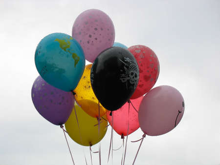 Group of colorful helium-filled balloons over sky background photo
