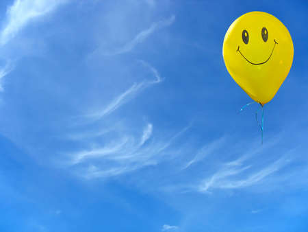 Smile yellow balloon over blue sky with clouds Standard-Bild
