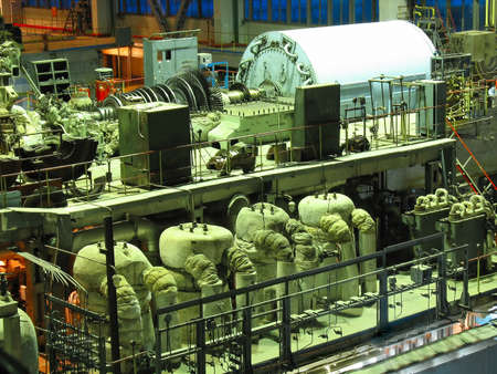 power generation: Power generator steam turbine during repair, machinery, pipes, tubes at a power plant, night scene