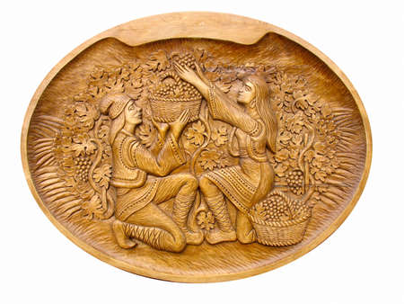 gather grapes scene on a wooden bass-relief isolated over white photo