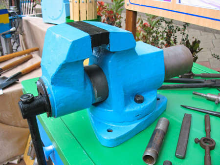 Old blue table mechanical vise clamp with instruments photo