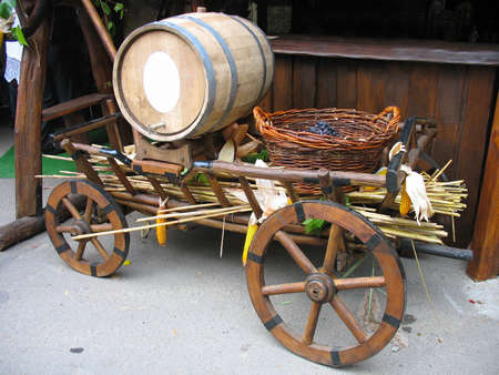 Old wooden cart with wooden barrel and grapes basket photo