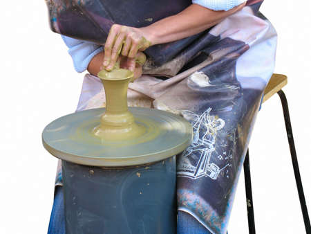 hands of a potter, creating an earthen jar on the circle, isolated photo