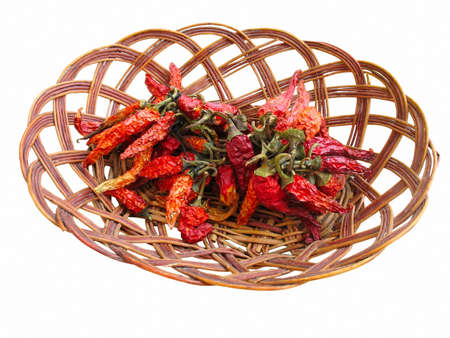 chiles secos: Dried Red Hot Chili Peppers en cesta de madera aislada en un fondo blanco Foto de archivo