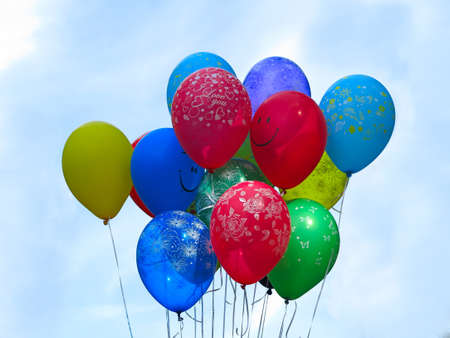 Flying colorfull balloons over blue sky background photo
