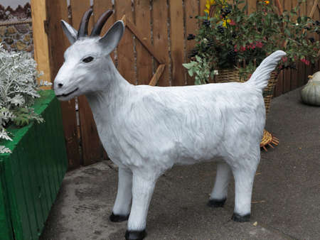 Simple white goat figurine in a garden photo