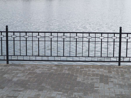 Metal fence over water background on the waterfront photo