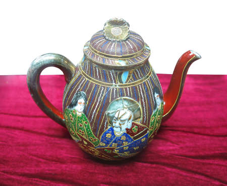 Decorated ancient colorful chinese ceramic teapot on red background photo