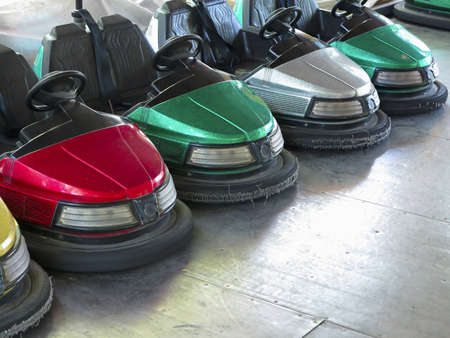 swab: colored electric cars in amusement park waiting for action