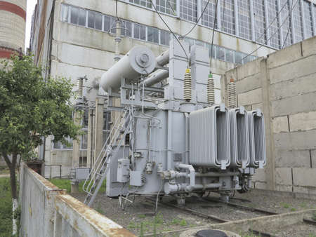 amp tower: Huge industrial high-voltage substation power transformer on rails at power plant Stock Photo