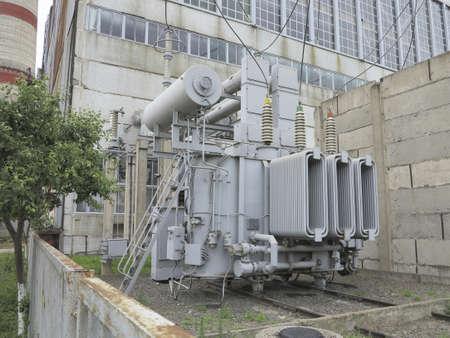 Huge industrial high-voltage substation power transformer on rails at power plant Standard-Bild