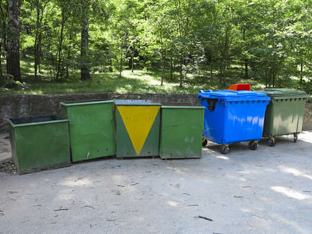 forest management: Old and new colorful garbage containers in a park Stock Photo