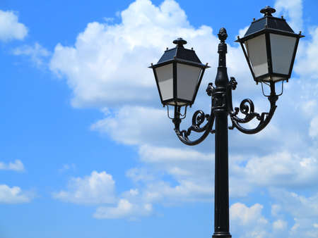 lampposts: Old street decorated lamppost against cloudy blue sky background Stock Photo