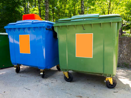 New colorful plastic garbage containers in a park photo