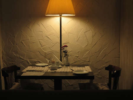 Romantic dinner table for couple served in restaurant with dim lights photo