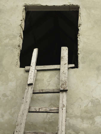cuve: Old wooden vintage cuve ladder near a wall concept Stock Photo