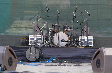 Drums set, powerful speakers, amplifiers and equipment on stage photo