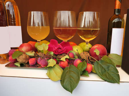 Three wine glasses bottles rose apples and nuts on table composition photo