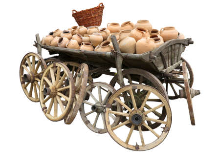 Old wooden cart full of clay pottery, wheels and wicker basket isolated over white background photo
