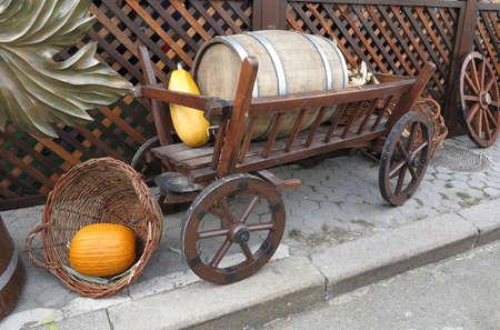 carreta madera: Carro de madera de la vendimia con el barril de vino, cesta de malvado y calabaza aislado más de blanco