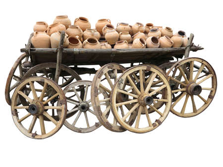 Old wooden cart full of clay pottery and wheels isolated over white background photo