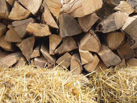 Background of dry chopped firewood logs in a pile and hay photo