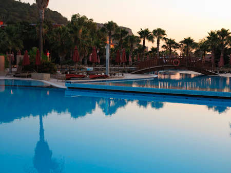 Luxury swimming pool and palms in the tropical resort hotel in the sunset