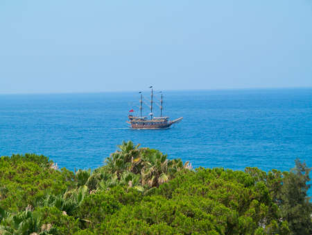 Vintage wooden pirate old ship in blue sea photo