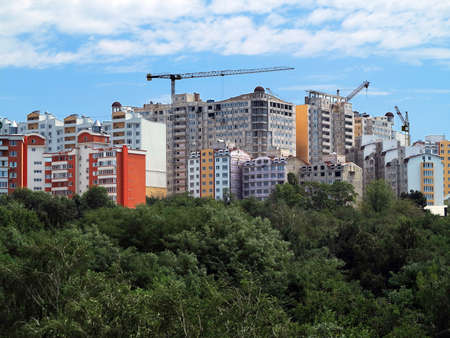 house under construction: Residential modern apartment house building, green forest and blue sky Stock Photo