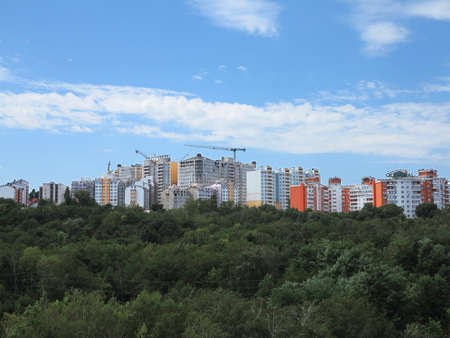 condominium complex: Residential modern apartment house building, green forest and blue sky Editorial