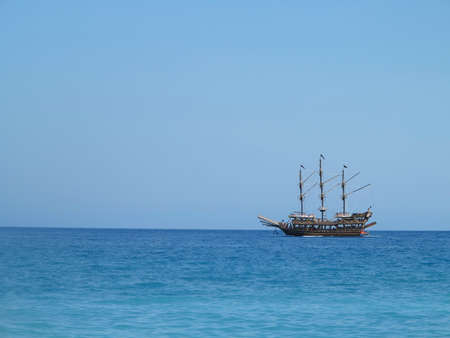 Old wooden pirate old ship in blue sea photo