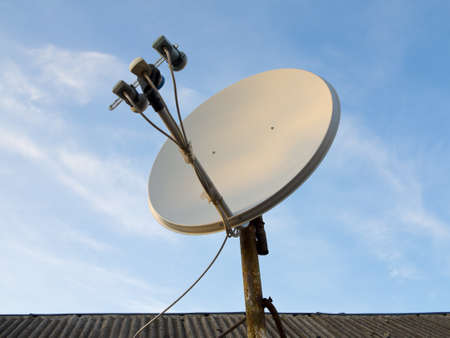 antenna: Satellite dish antenna over blue sky and roof background