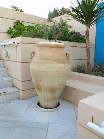greek pot: Vaso greco marrone e fiori su strada nel villaggio cretese Archivio Fotografico
